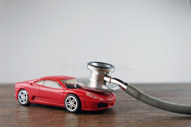 听诊器和汽车在木桌上,汽车核对的概念 免版税图库摄影