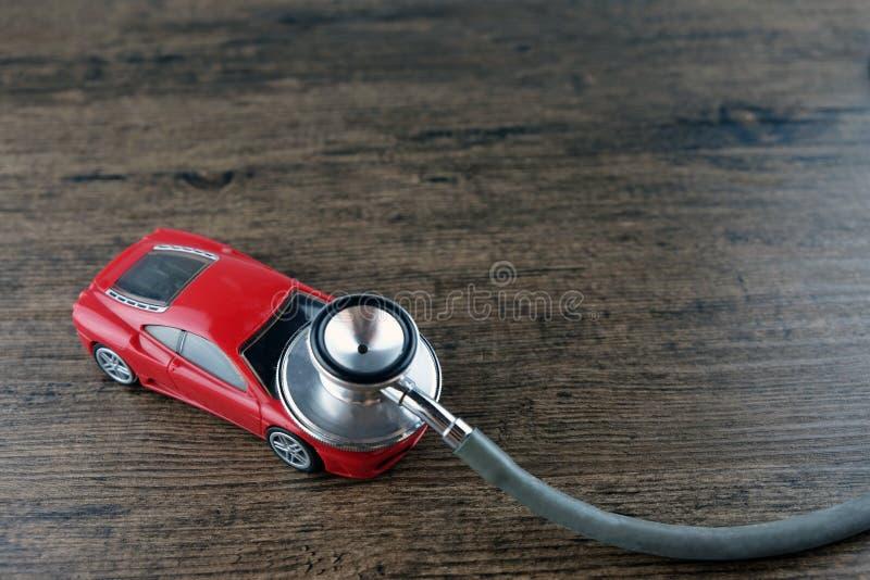 听诊器和汽车在木桌上,汽车核对的概念 库存图片