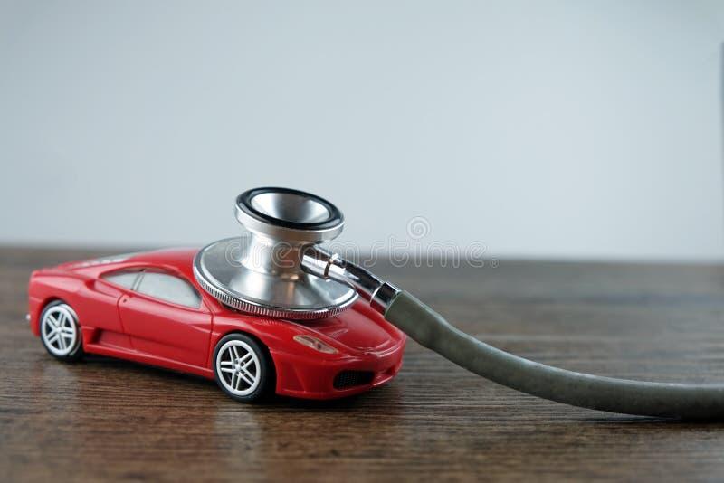 听诊器和汽车在木桌上,汽车核对的概念 库存照片