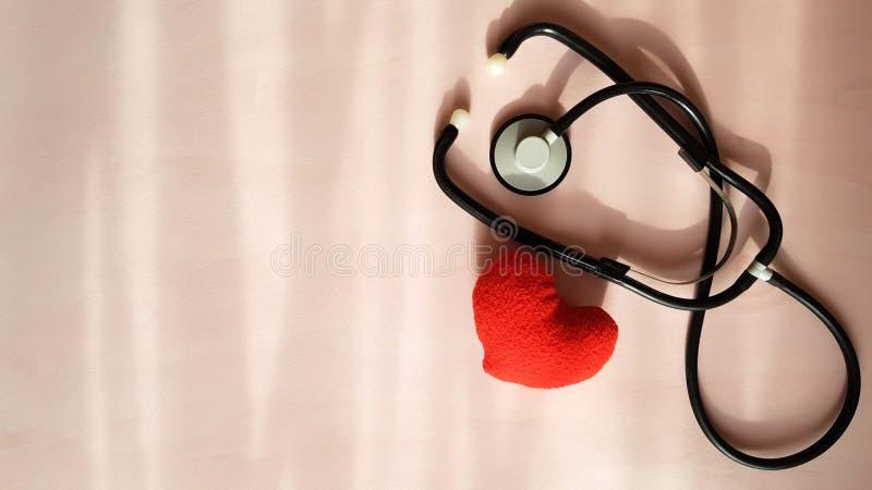 听诊器和红心在自然光来源背景,顶视图 E 图库摄影