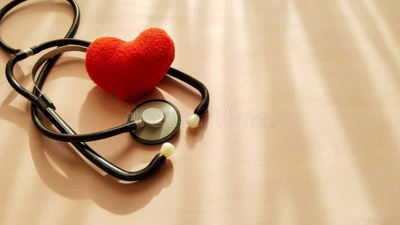 听诊器和红心在自然光来源背景,顶视图 E 库存图片