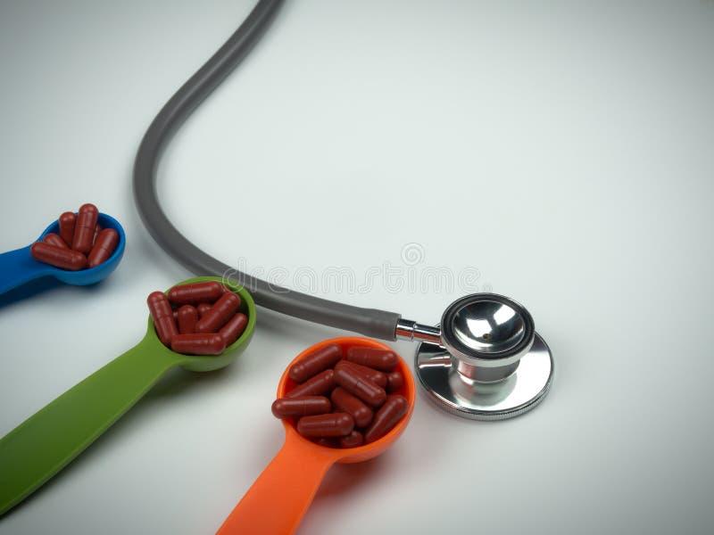 听诊器和红色在五颜六色的量匙的胶囊药片在白色背景 免版税库存照片