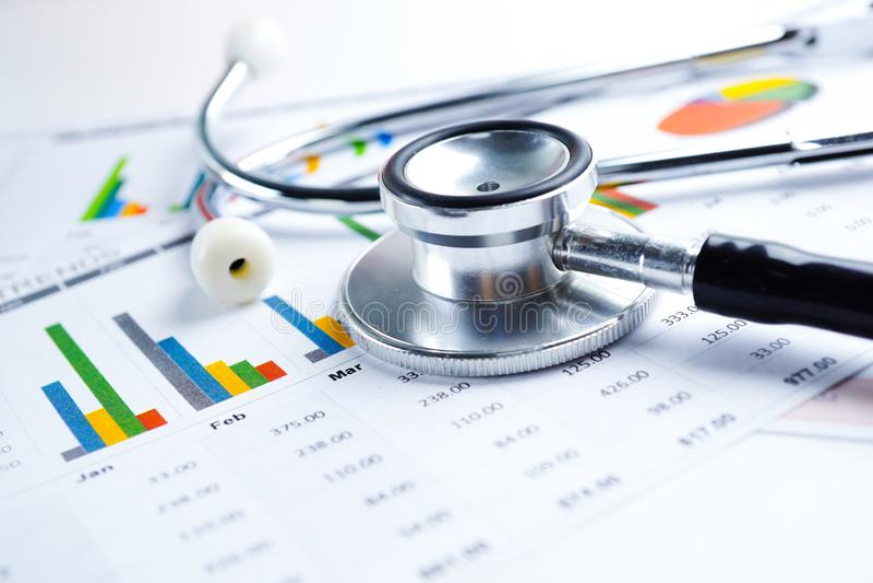 听诊器和美元钞票在图座标图纸,财政,帐户、统计和企业数据概念 库存图片