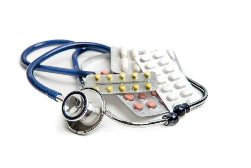 听诊器和药片在白色 图库摄影