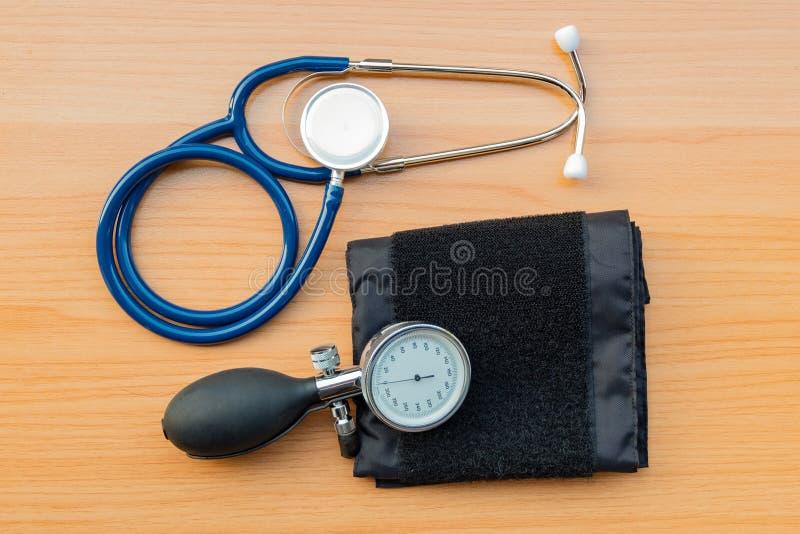 听诊器和血压计在木纹理背景 免版税库存图片