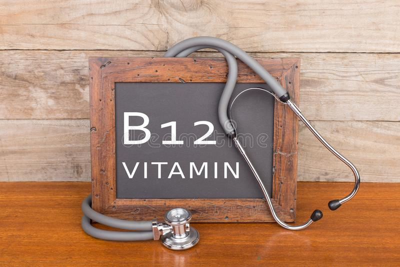 听诊器和黑板有文本& x22的; 维生素B12 & x22;在木背景 免版税库存图片