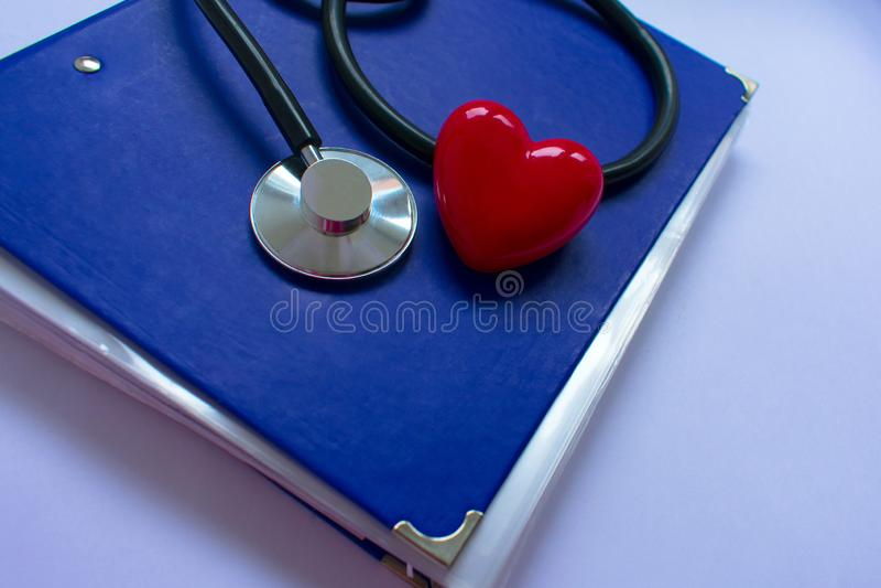 听诊器和heartn在黑背景 免版税库存图片