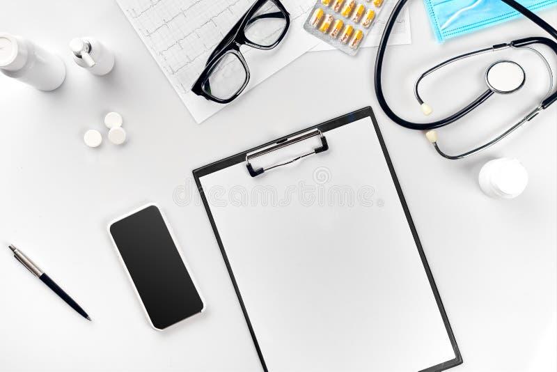 听诊器在医生办公室 医生` s书桌桌,在剪贴板的白纸顶视图有笔的 复制空间 免版税库存图片