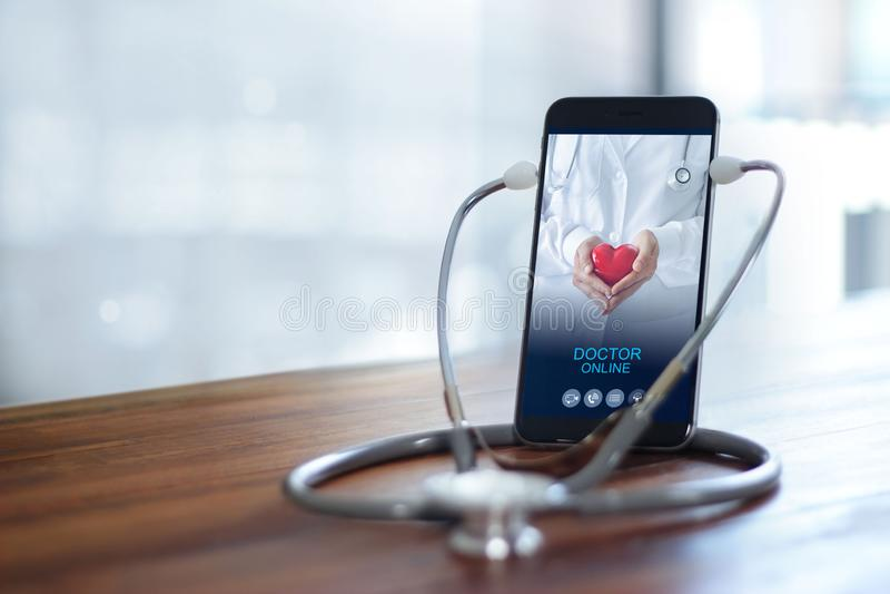 听诊器带智能手机,医生通过手机屏幕检查健康 网上医疗咨询、网上医疗 免版税图库摄影