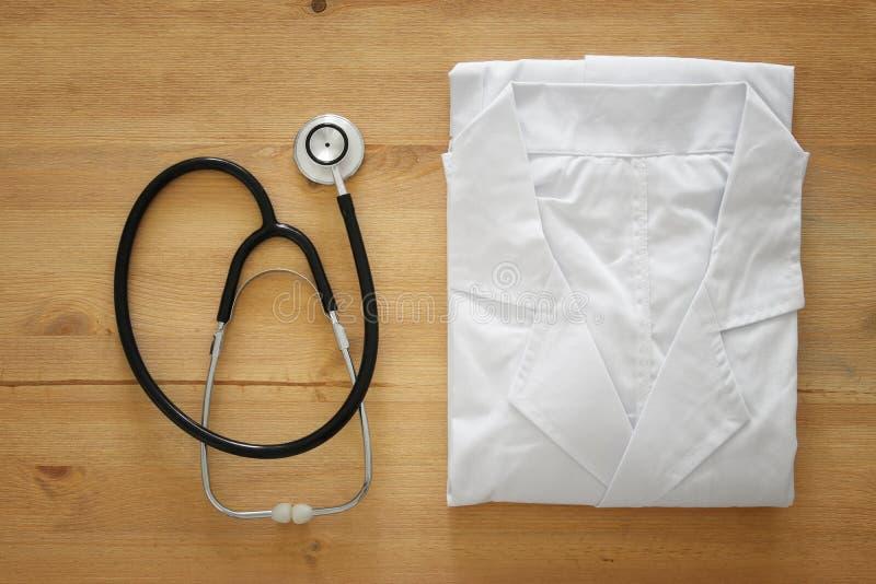 听诊器的图象和医生涂上在木书桌 医疗概念 库存图片