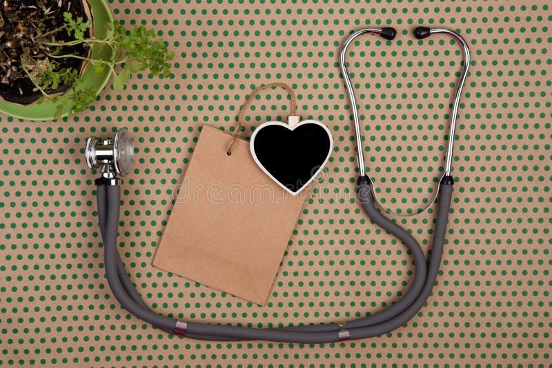 听诊器,以心脏,购物袋的形式空白的黑板 库存图片