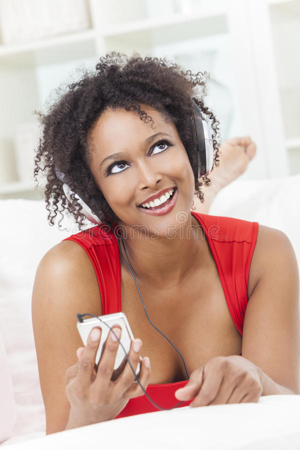 听MP3播放器耳机的非裔美国人的女孩 库存照片