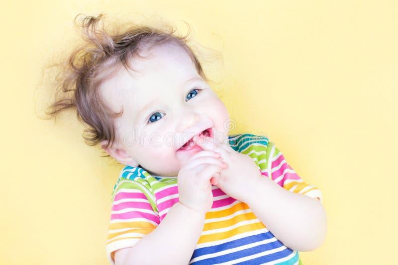 吮在她的手指的滑稽的女婴 免版税图库摄影