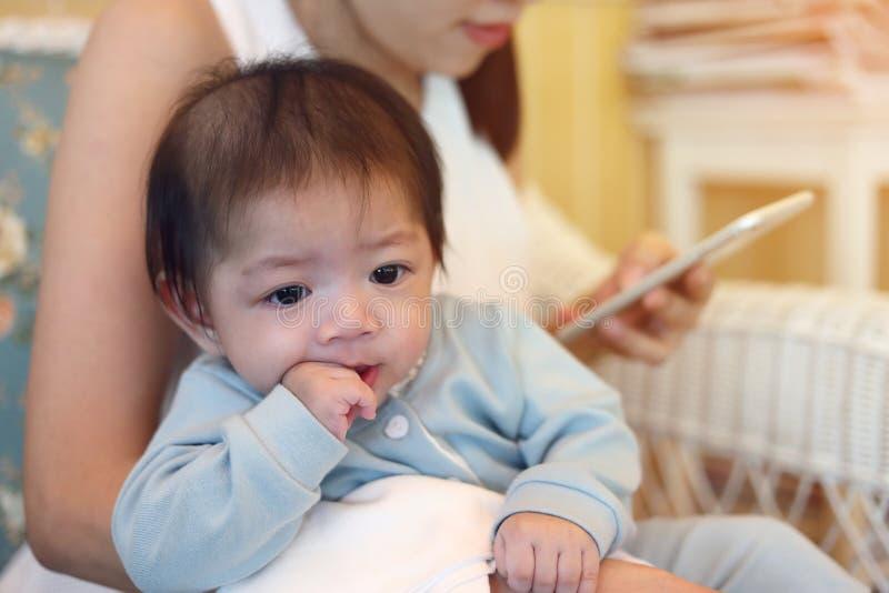 吮有母亲的逗人喜爱的男婴手指手 免版税库存图片
