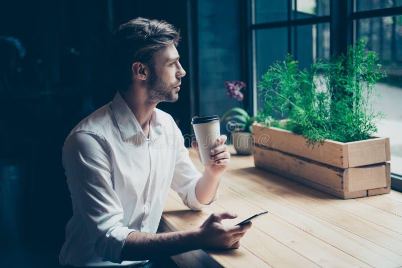 启发和咖啡的时刻 年轻自由职业者认为,他作梦并且享用,坐在一个现代咖啡馆在风附近 免版税库存照片