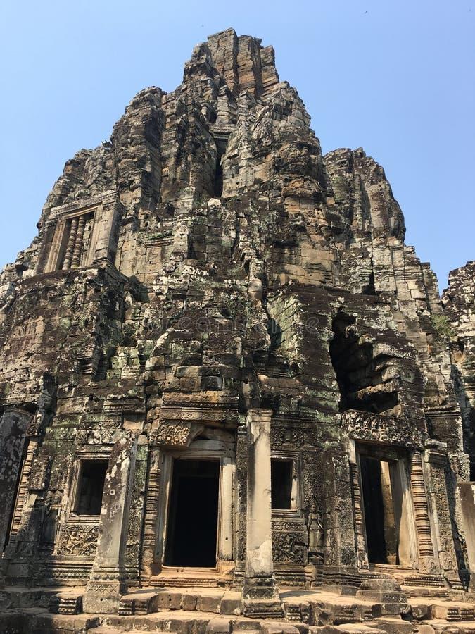 吴哥窟在暹粒市,柬埔寨吴哥窟是复杂最大的印度寺庙和最大的宗教纪念碑在世界上 石面孔在Bayon高棉寺庙古老废墟雕刻了  库存照片