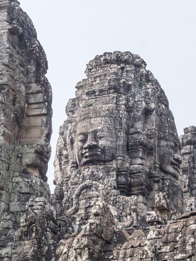吴哥窟寺庙由大国王的面孔装饰了 在暹粒市,柬埔寨 免版税库存图片