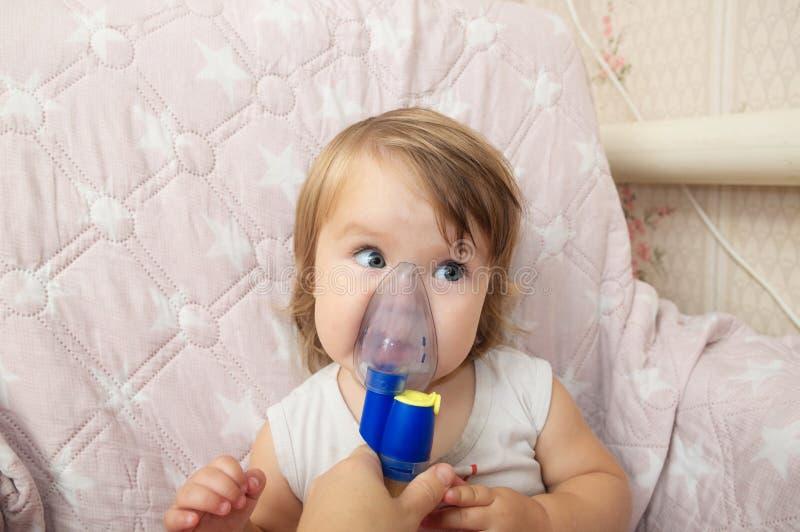 吸入的病态的女婴用途雾化器面具,由肺炎的呼吸孩子的做法或咳嗽 图库摄影