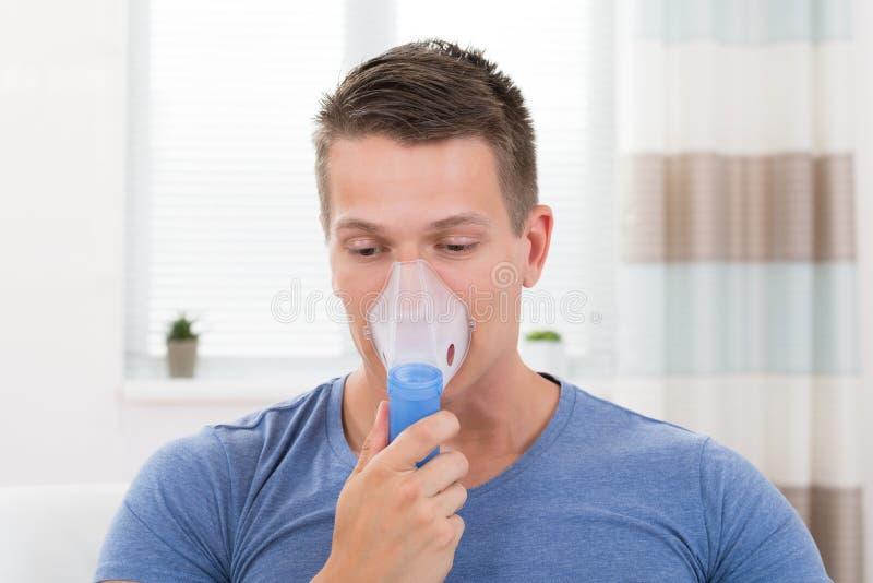 吸入通过吸入器面具的人 图库摄影
