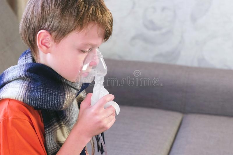 吸入通过吸入器面具的病的逗人喜爱的男孩 为治疗使用雾化器和吸入器 侧视图 免版税库存图片