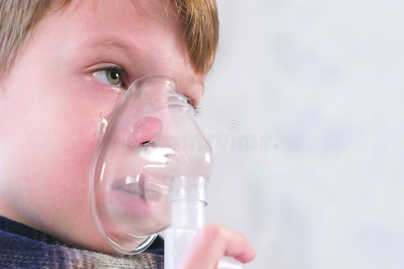 吸入通过吸入器面具,面孔特写镜头侧视图的病的男孩 为治疗使用雾化器和吸入器 库存图片