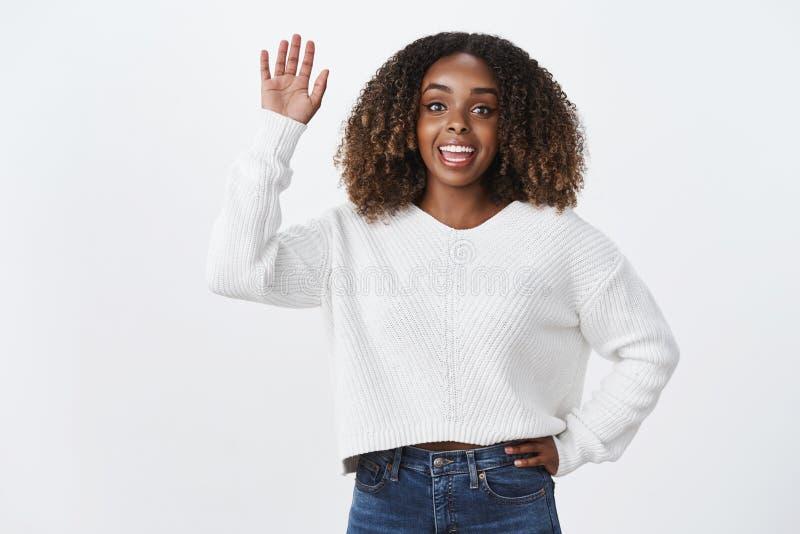 吸引人友好的善社交的活泼的非裔美国人可爱的妇女说喂挥动的被上升的手你好姿态问候 库存图片