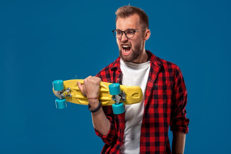 吸引人快乐的年轻有胡子的人在方格的衬衣、白色T恤杉和玻璃穿戴了,与黄色滑板 免版税库存照片
