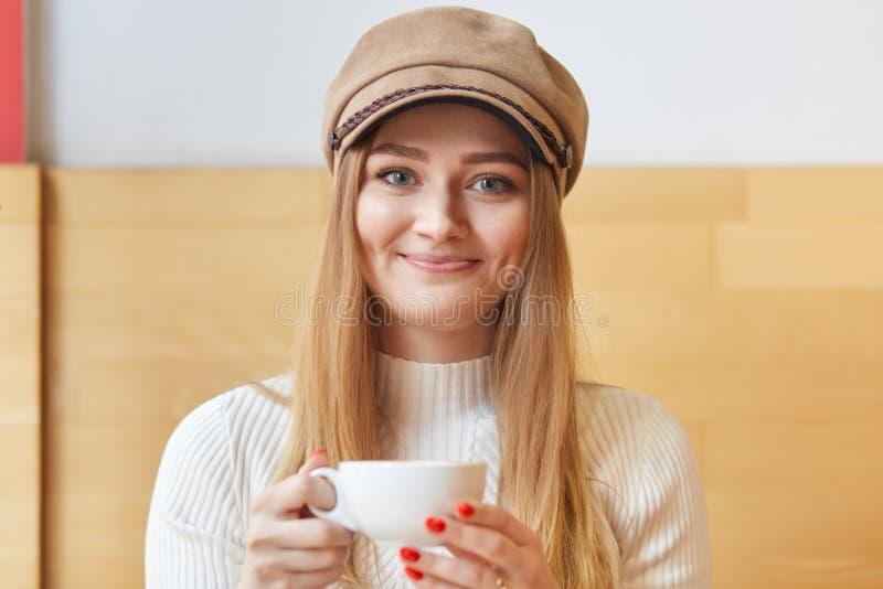 吸引人甜女性画象在两只手,微笑,神色中采取在咖啡馆的休息,拿着杯子热的饮料直接地秘密审议 免版税库存图片