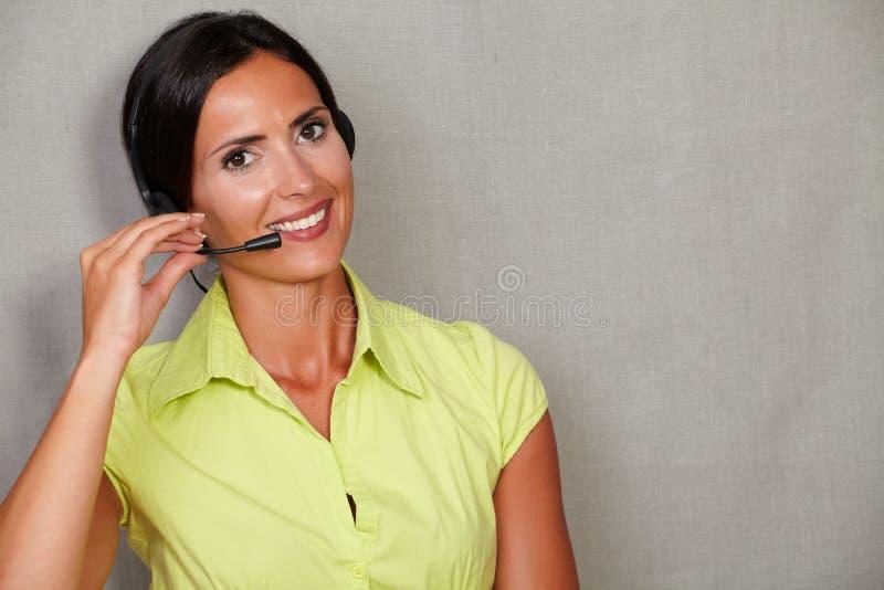 吸引人年轻女实业家谈话在耳机 库存图片