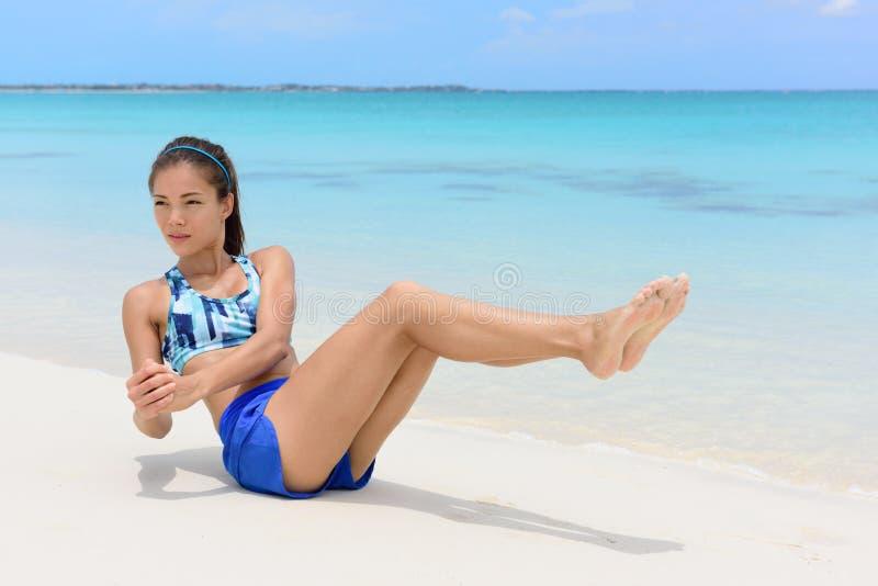 吸收锻炼-解决在海滩的健身妇女 库存照片