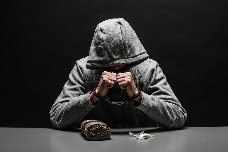 吸毒者被拘捕了为药物使用在桌上 遭受在深黑色背景的瘾 免版税库存照片