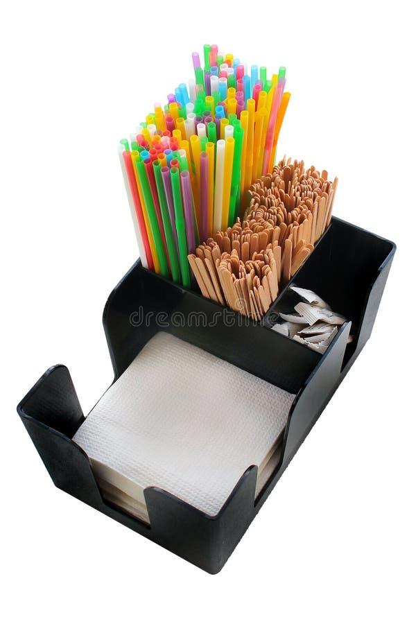 吸管、木棍子和餐巾在箱子 免版税库存图片