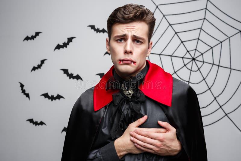 吸血鬼万圣夜概念-英俊的白种人画象吸血鬼握在心脏的万圣夜服装的手 免版税图库摄影