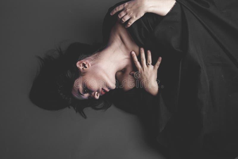 吸血鬼,有大黑布料的哥特式黑暗的妇女在灰色backgr 图库摄影