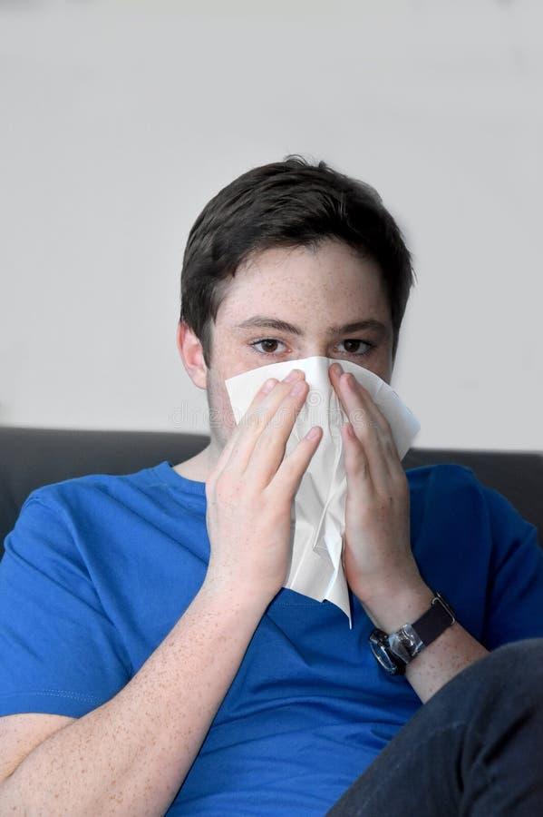 吹他的鼻子的病的十几岁的男孩 免版税库存图片