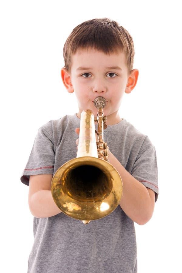吹入喇叭的年轻男孩 库存照片