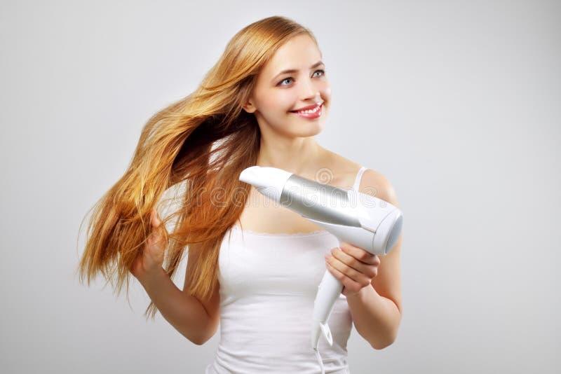 吹动烘干机干燥女孩头发她微笑 免版税库存图片