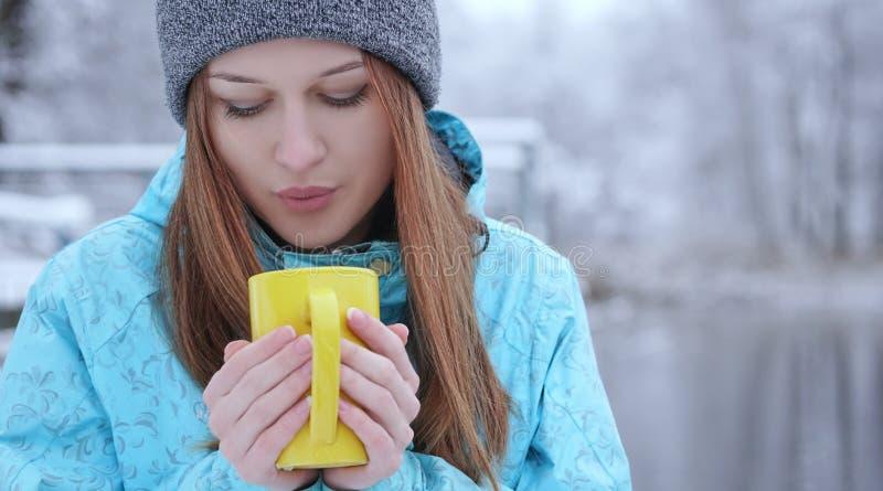 吹在一份热的茶或咖啡的年轻美丽的女孩站立在冬天湖的岸 免版税库存图片
