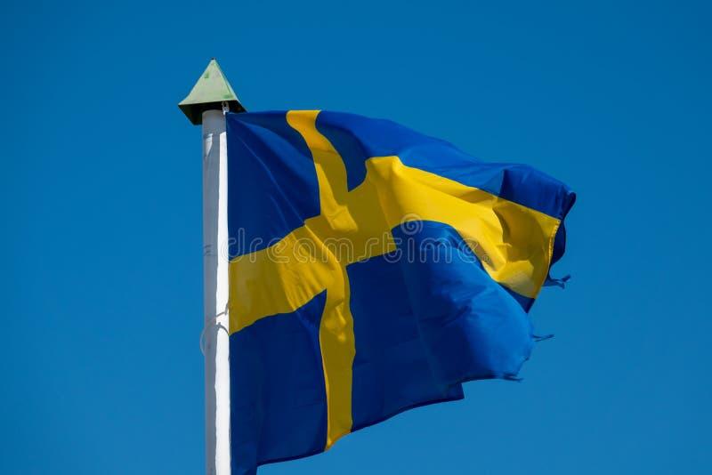 吹在天空蔚蓝前的瑞典的旗子 库存照片