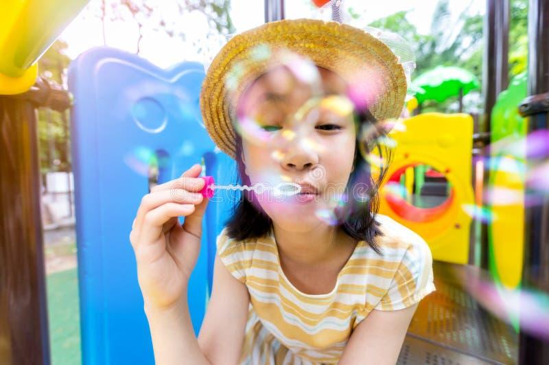 吹在操场的亚裔女孩泡影室外和看照相机,愉快的逗人喜爱的孩子使用与肥皂泡 库存照片