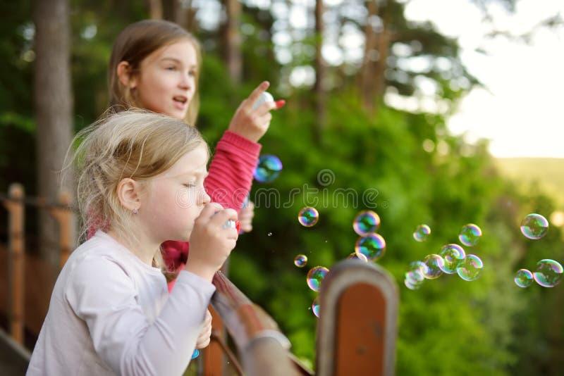 吹在日落户外的逗人喜爱的女孩肥皂泡在美好的夏日 免版税图库摄影