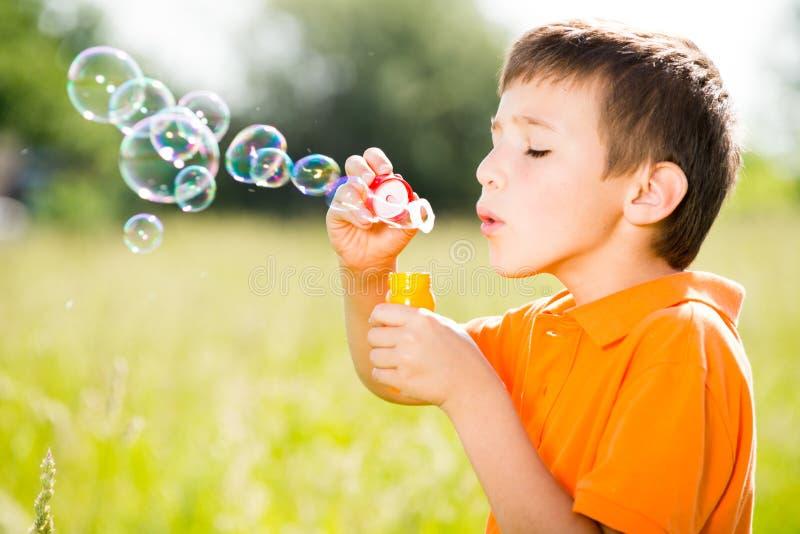 吹在自然的白种人男孩肥皂泡 免版税库存照片