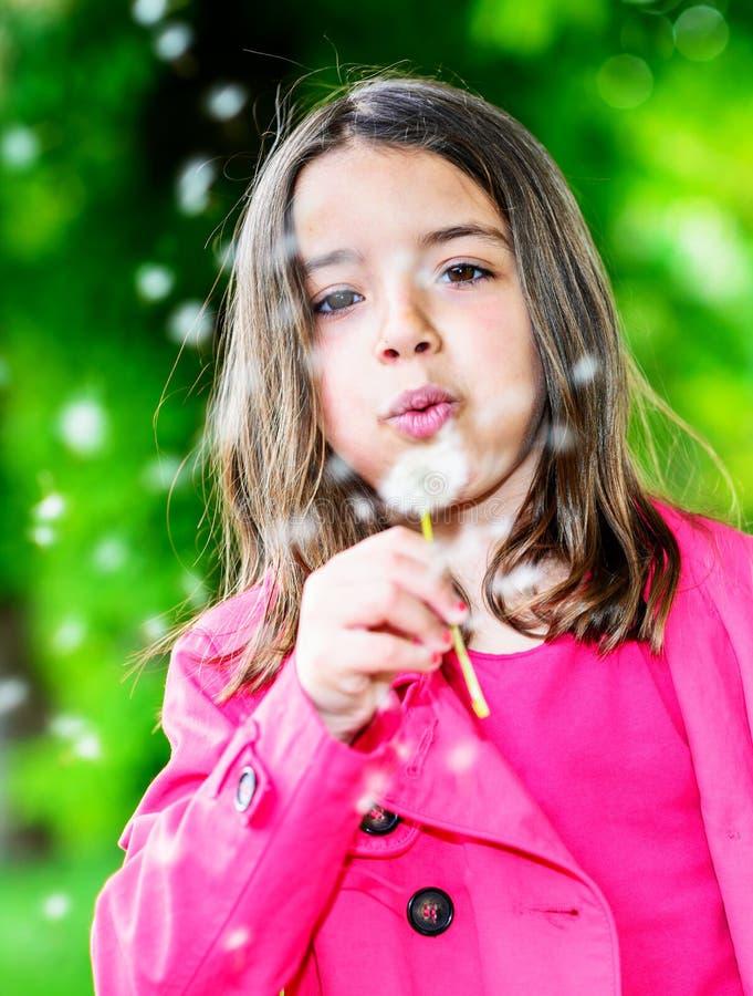 吹在花的逗人喜爱的孩子画象站立在公园 免版税库存图片