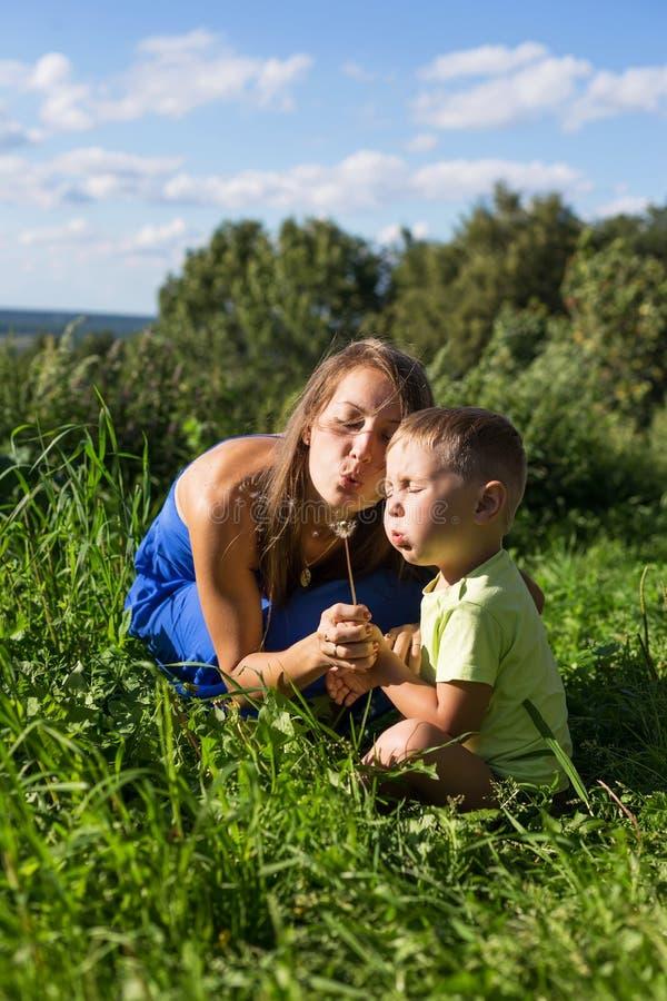 吹在蒲公英的母亲和儿子户外 免版税库存照片
