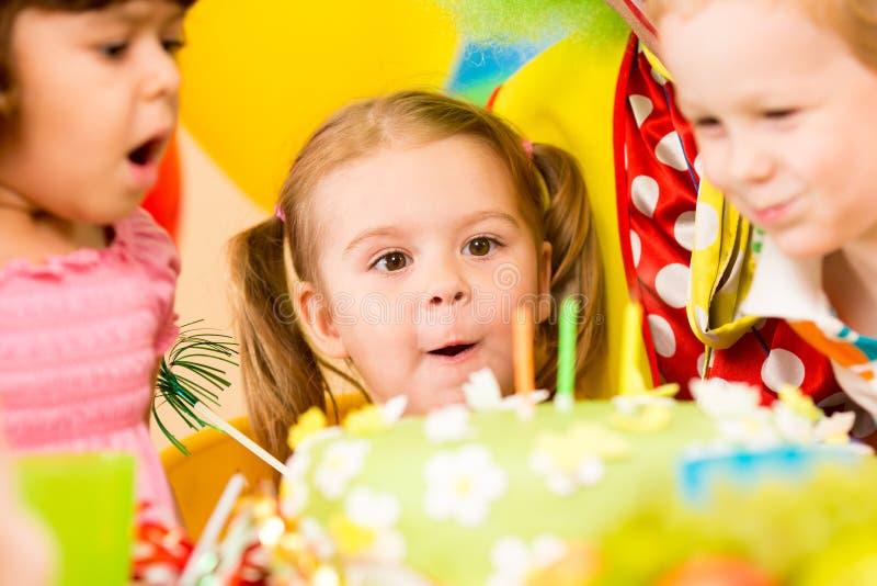 吹在蛋糕的滑稽的孩子蜡烛 免版税库存图片