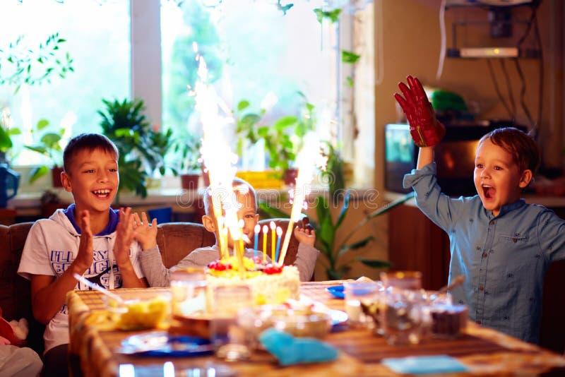 吹在蛋糕的高兴孩子蜡烛,当在家时庆祝生日聚会 免版税库存图片