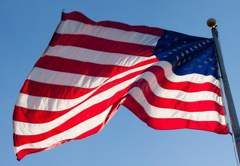 吹在风的美国国旗反对蓝天