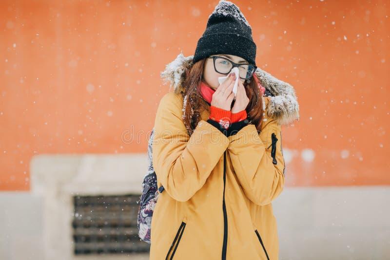 吹她的与组织的年轻女人鼻子室外在冬天 的少妇病与流感在一个冬日 图库摄影