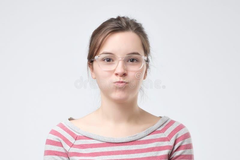 吹她的面颊高兴地的逗人喜爱的俏丽的妇女获得乐趣 免版税库存图片