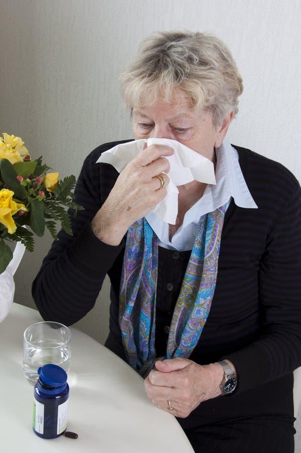 吹她的鼻子前辈妇女 免版税库存图片